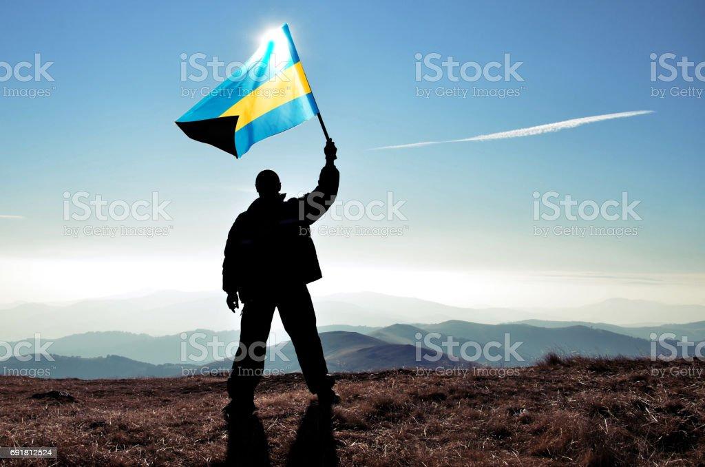 Successful silhouette man winner waving Bahamas flag on top of the mountain peak stock photo