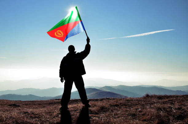 successful silhouette man winner waving eritrea flag on top of the mountain peak - eritrea stock photos and pictures
