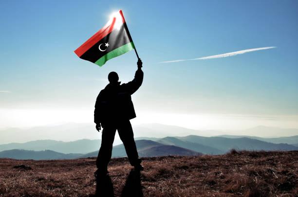 Successful silhouette man winner waving Libya flag on top of the mountain peak stock photo