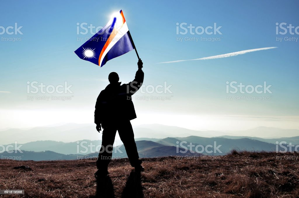 Successful silhouette man winner waving Marshall Islands flag on top of the mountain peak stock photo