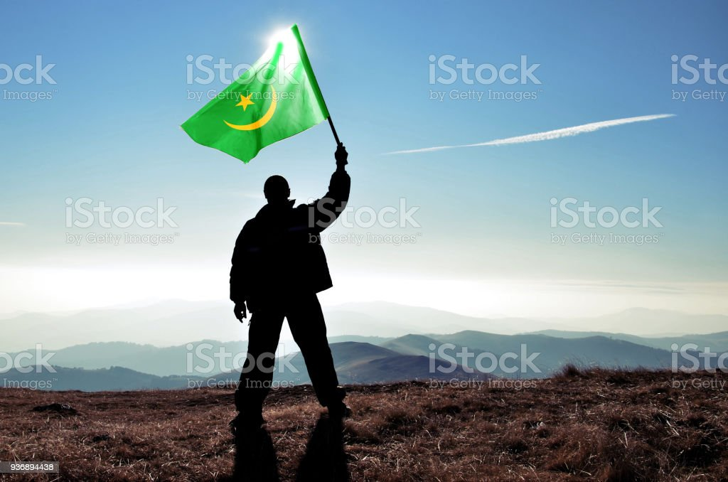 Successful silhouette man winner waving Mauritania flag on top of the mountain peak stock photo