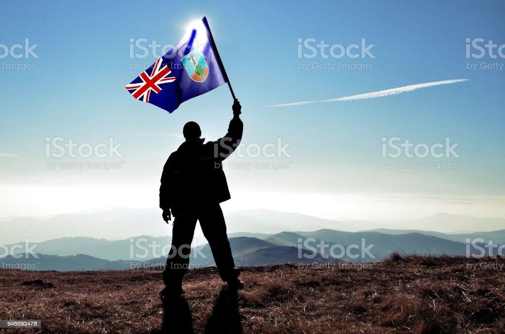 Successful silhouette man winner waving Montserrat flag on top of the mountain peak stock photo