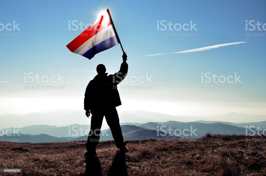 Successful silhouette man winner waving Netherlands flag on top of the mountain peak stock photo