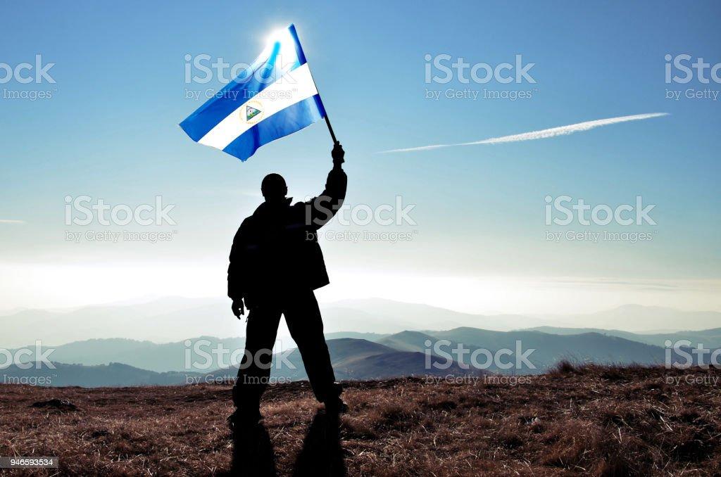 Successful silhouette man winner waving Nicaragua flag on top of the mountain peak stock photo