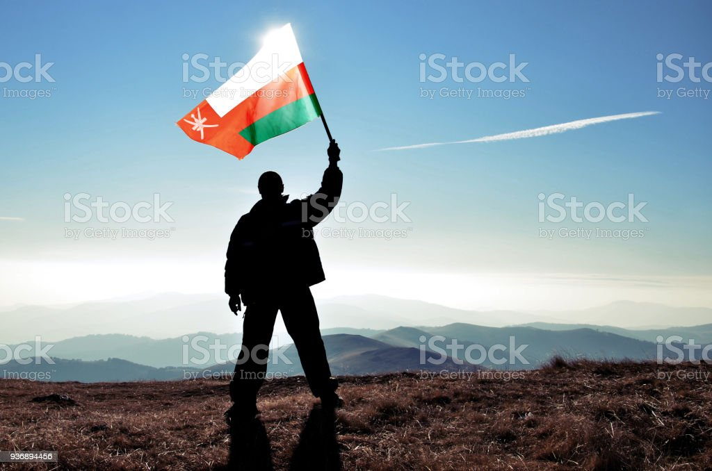 Successful silhouette man winner waving Oman flag on top of the mountain peak stock photo