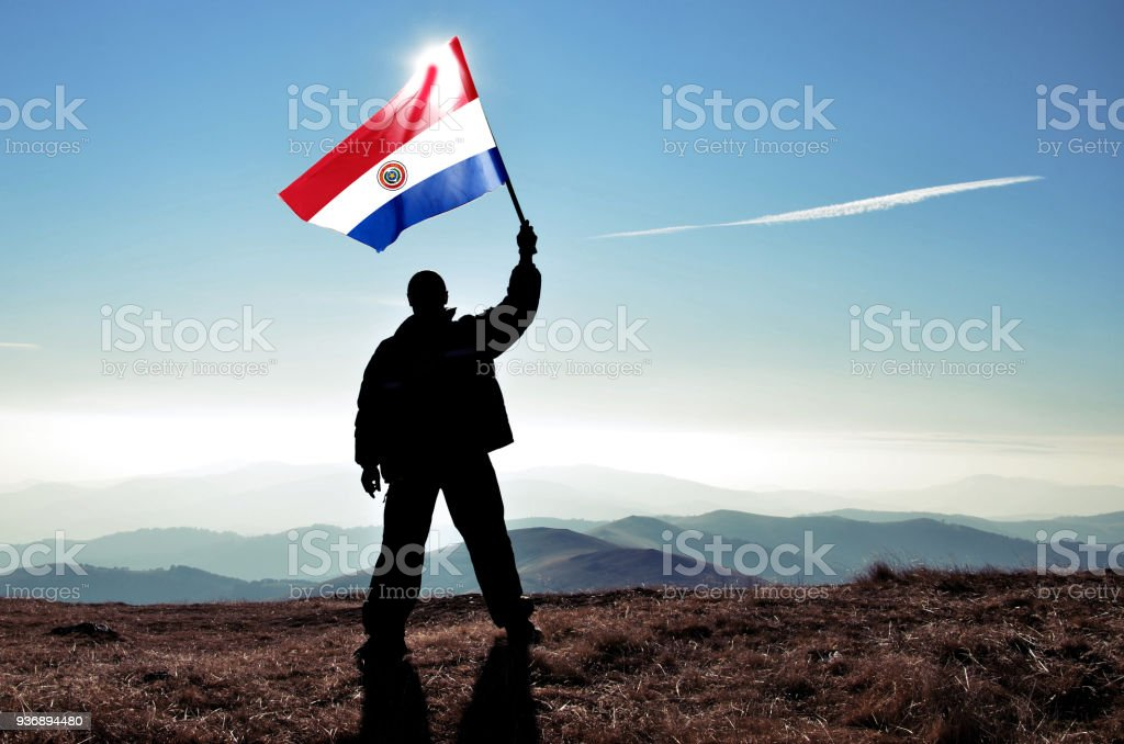 Successful silhouette man winner waving Paraguay flag on top of the mountain peak stock photo