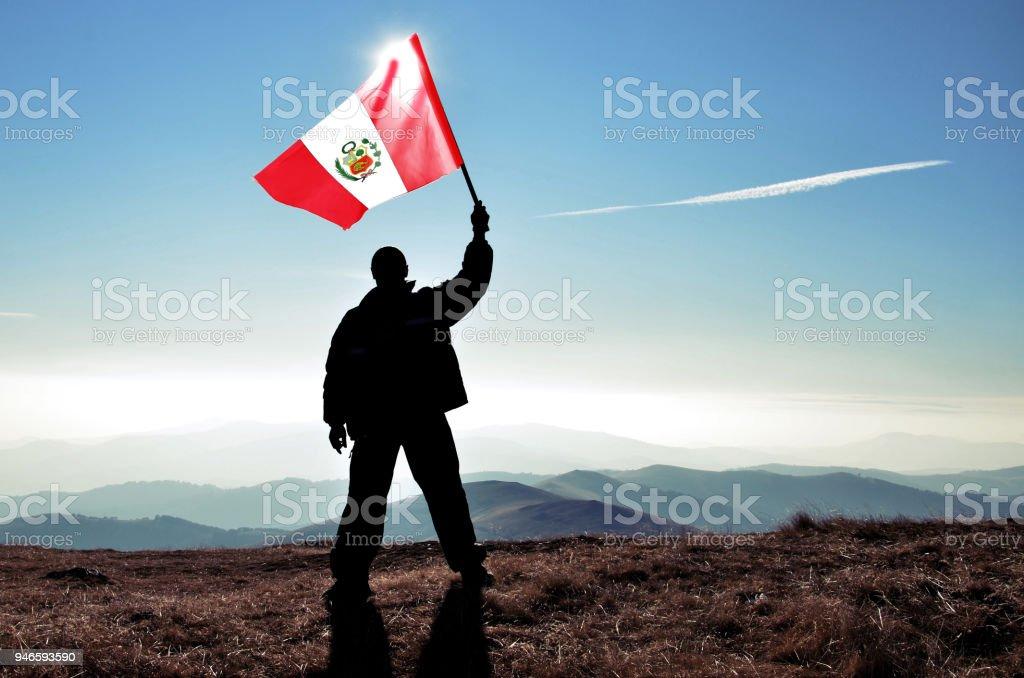 Successful silhouette man winner waving Peru flag on top of the mountain peak stock photo