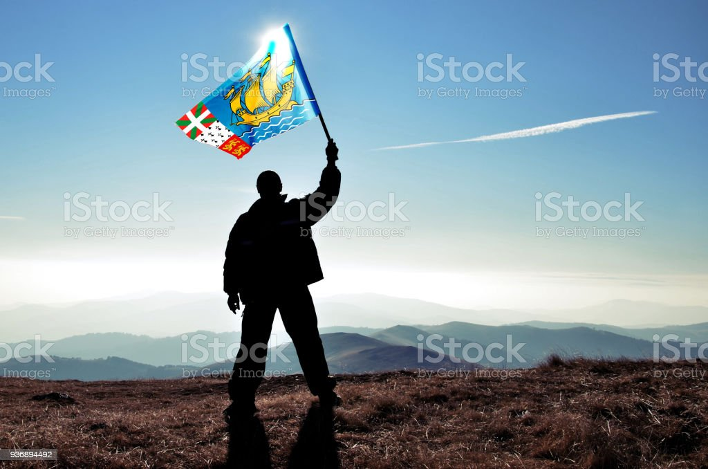 Successful silhouette man winner waving Pierre and Miquelon flag on top of the mountain peak stock photo