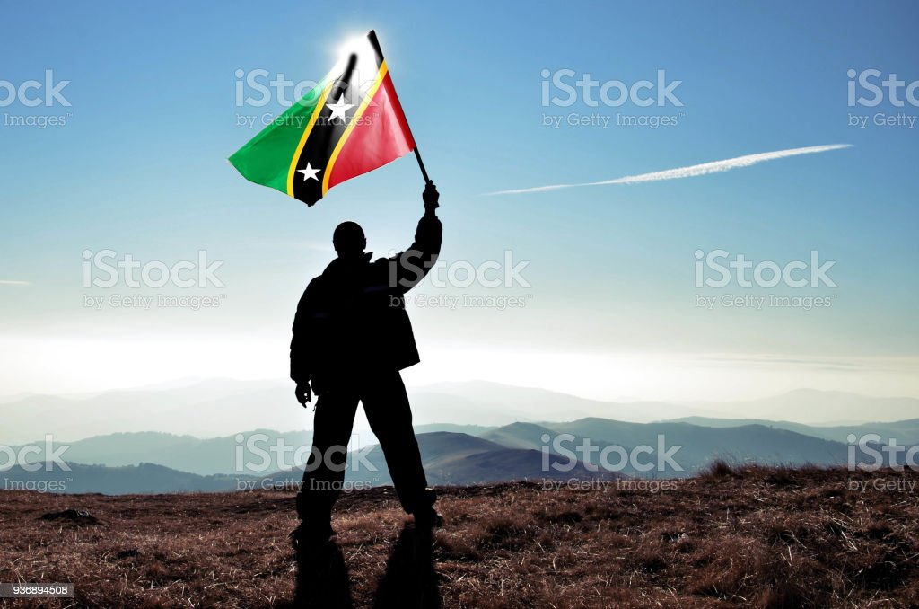 Successful silhouette man winner waving Saint Kitts and Nevis flag on top of the mountain peak stock photo