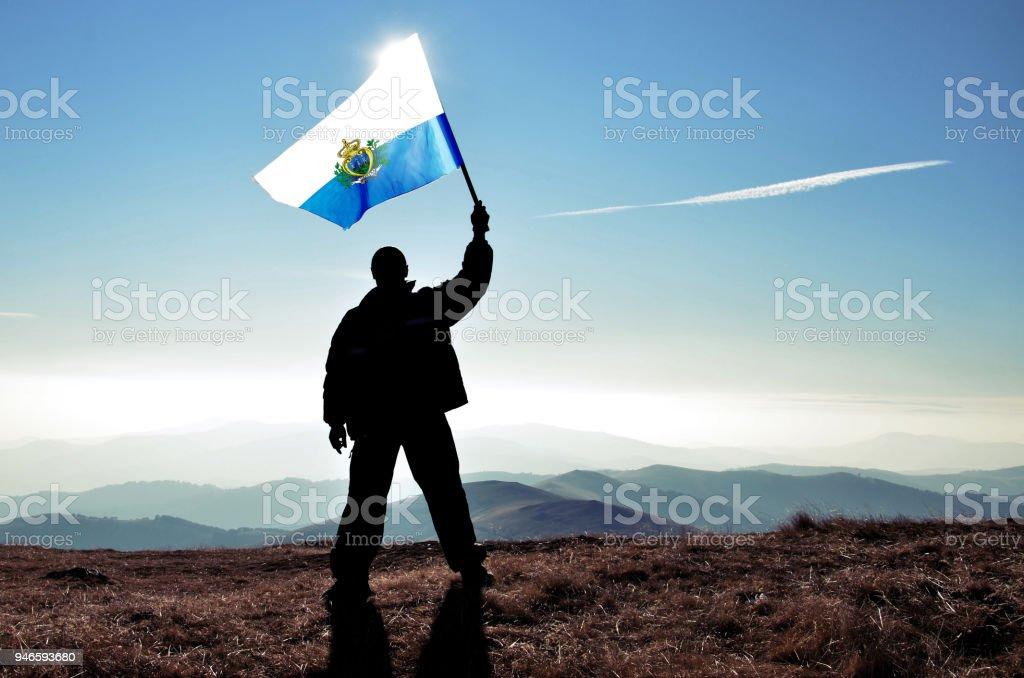 Successful silhouette man winner waving San Marino flag on top of the mountain peak stock photo