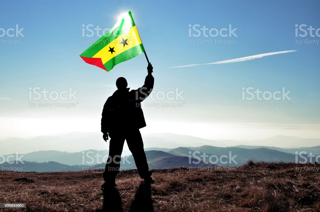 Successful silhouette man winner waving Sao Tome and Principe flag on top of the mountain peak stock photo
