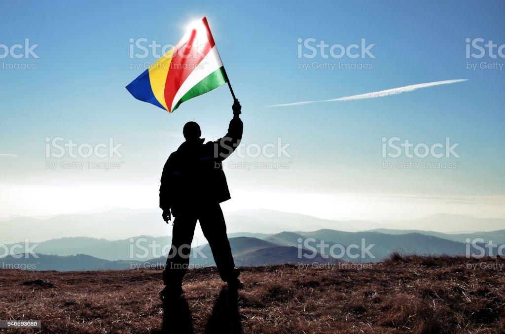 Successful silhouette man winner waving Seychelles flag on top of the mountain peak stock photo