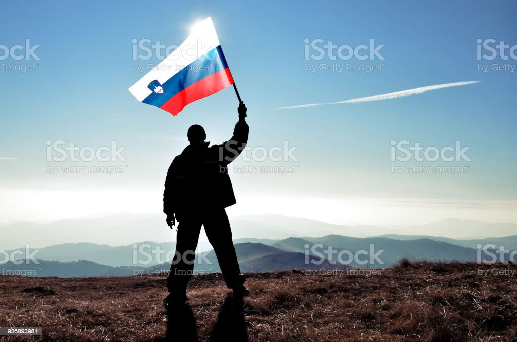 Successful silhouette man winner waving Slovenia flag on top of the mountain peak stock photo