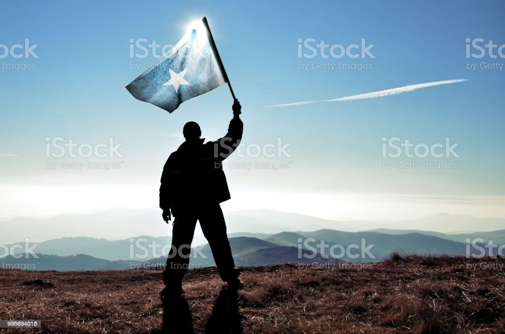 Successful silhouette man winner waving Somalia flag on top of the mountain peak stock photo