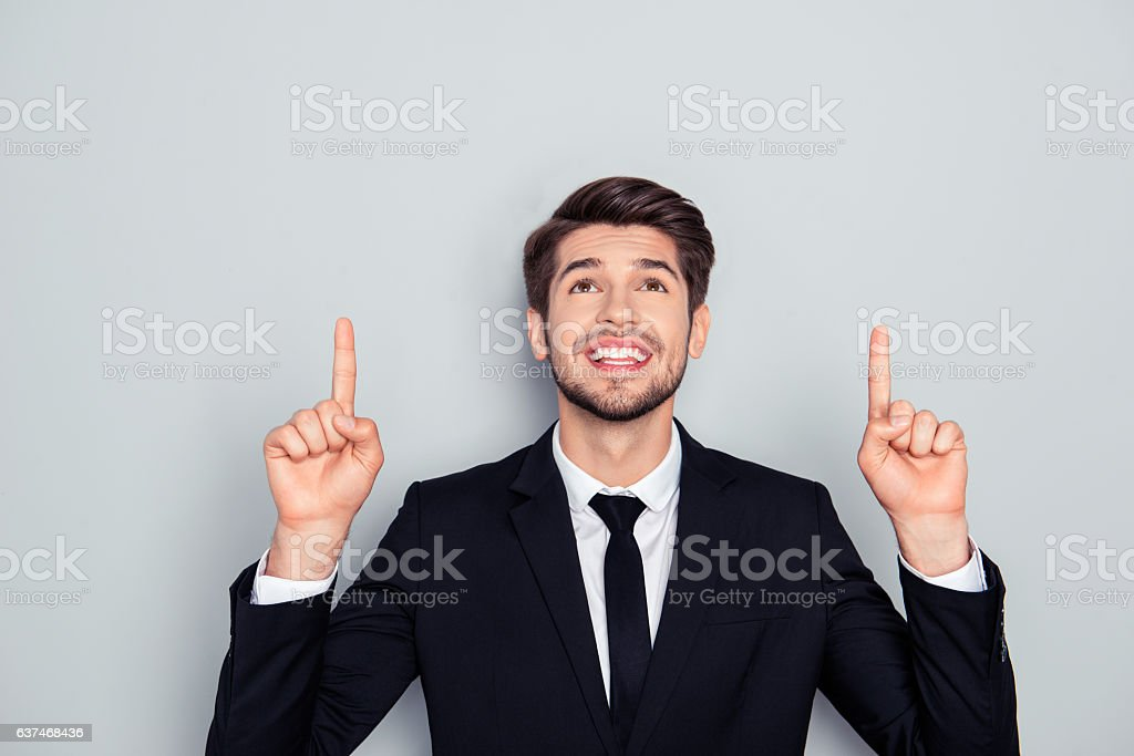 Successful smiling businessman with raised fingers pointing up stock photo