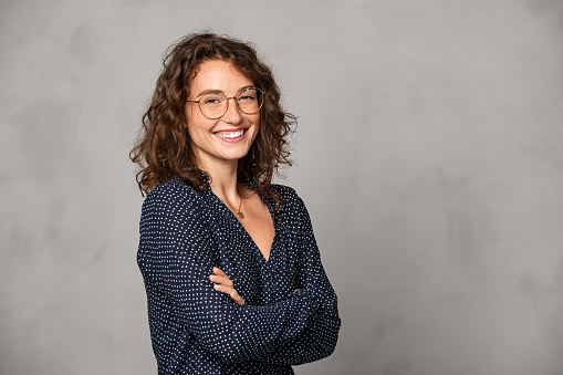 Confident young woman wearing eyeglasses and standing with folded arms on gray wall. Portrait of smiling businesswoman with arms crossed isolated against grey background with copy space. Proud university student girl with specs looking at camera.