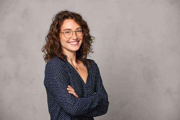 Successful smiling woman wearing eyeglasses on grey wall stock photo