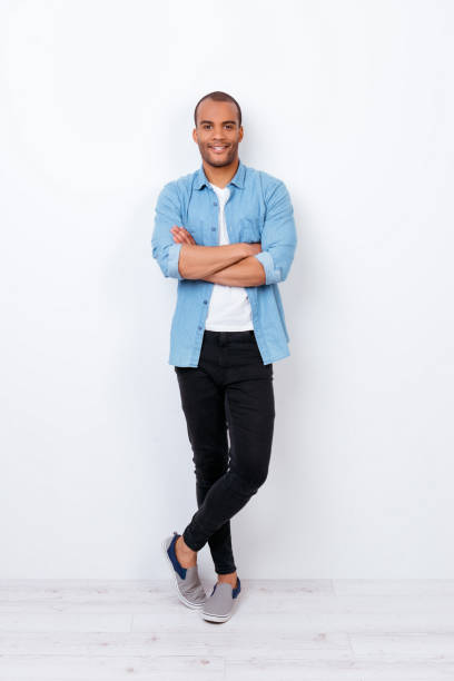 Successful smiling young handsome mulatto american student in trendy denim outfit on pure white background with crossed hands. So confident, attractive and smart stock photo