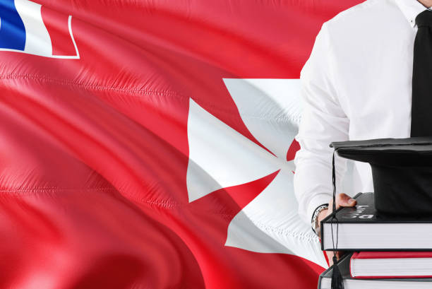 Successful student education concept. Holding books and graduation cap over Wallis And Futuna flag background. stock photo