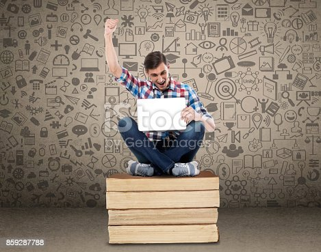 947303582 istock photo Successful student sitting with laptop on stack of books 859287788