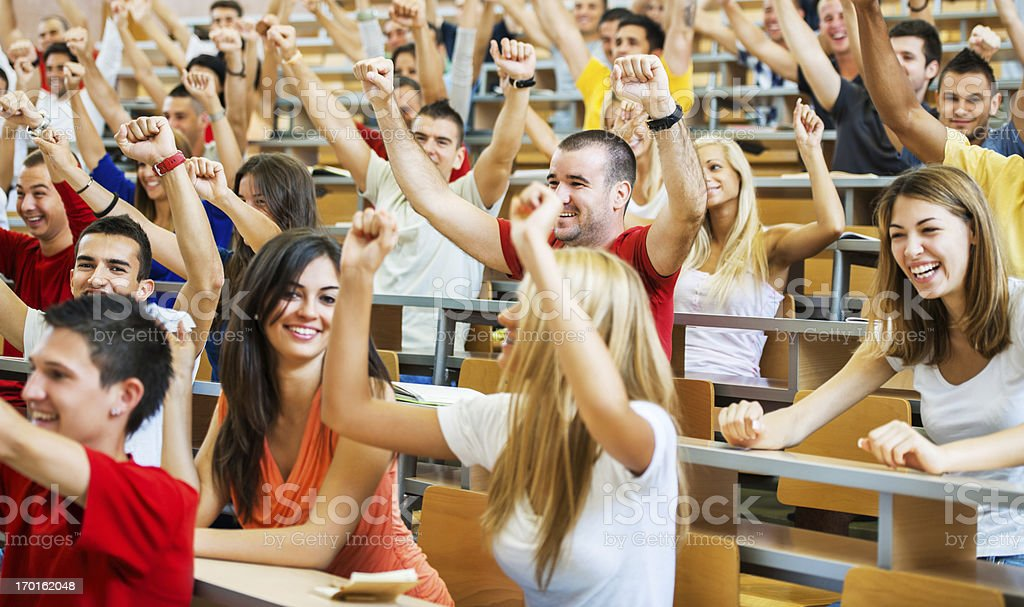 Successful students sitting with raised arms stock photo