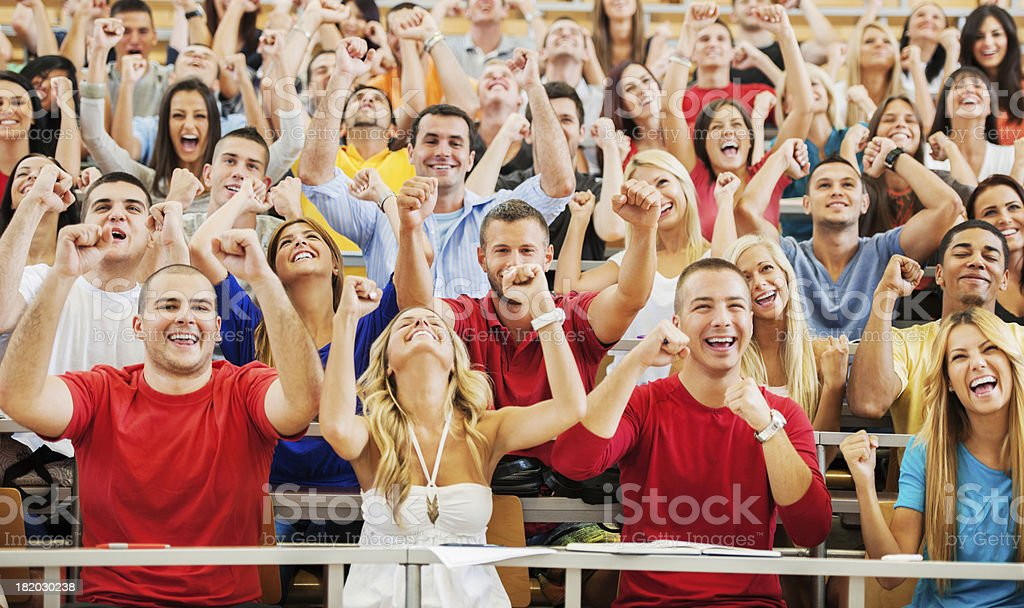 Successful students sitting with raised arms. stock photo