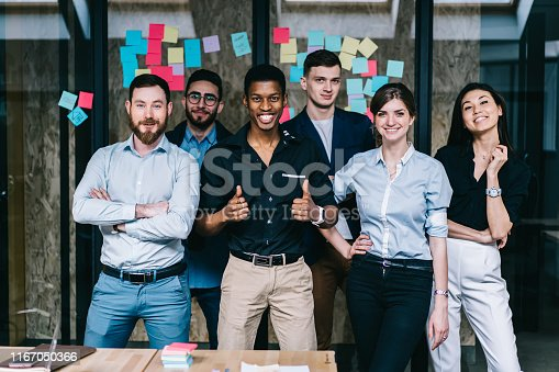 888892364istockphoto Successful team of multicultural young people dressed in formal wear smiling and showing ok at camera.Prosperous group of male and female diverse professionals standing in modern office interior 1167050366