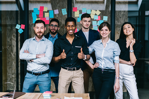 888892364 istock photo Successful team of multicultural young people dressed in formal wear smiling and showing ok at camera.Prosperous group of male and female diverse professionals standing in modern office interior 1167050366