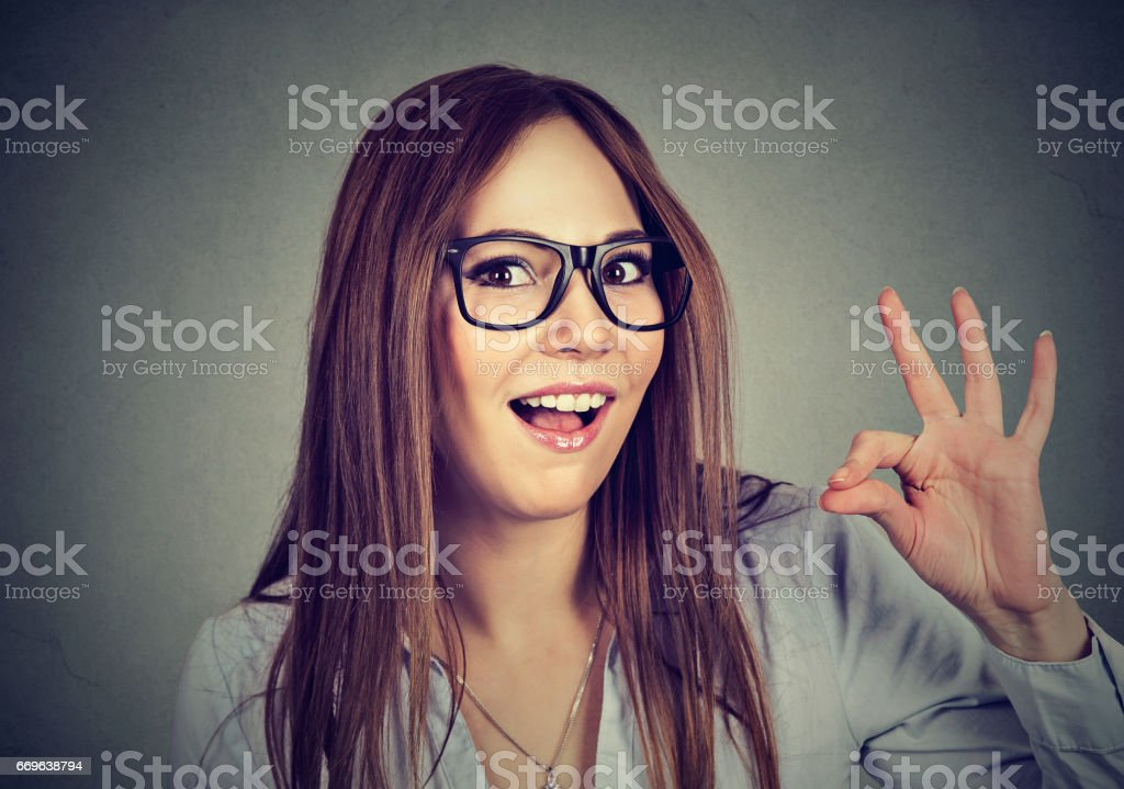 Successful teenager. Nerdy funny woman showing ok sign stock photo