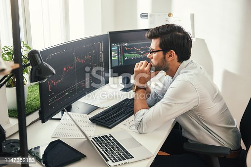 Successful trader. Back view of bearded stock market broker in eyeglasses analyzing data and graphs on multiple computer screens while sitting in modern office. Stock exchange. Trade concept. Investment concept