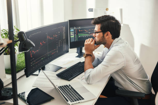 successful trader. back view of bearded stock market broker in eyeglasses analyzing data and graphs on multiple computer screens while sitting in modern office. - scambio commerciale foto e immagini stock