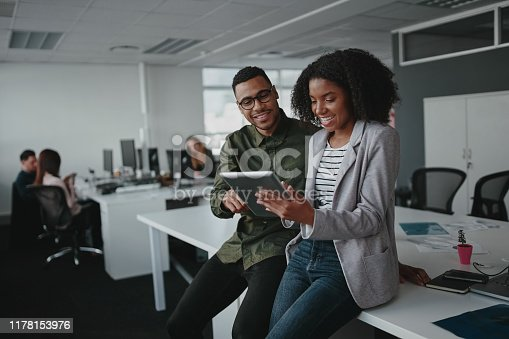 Successful african american business couple talking and using digital tablet