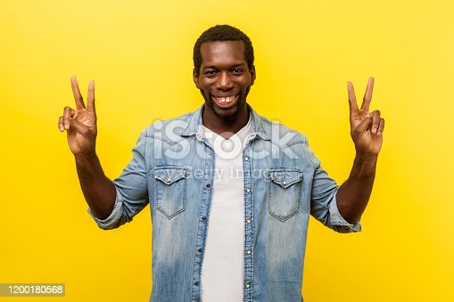 1012628232istockphoto Successful winner. Portrait of excited man showing v sign or peace. studio shot isolated on yellow background 1200180568