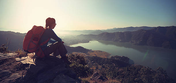successful woman backpacker enjoy the view at mountain peak - foto stock