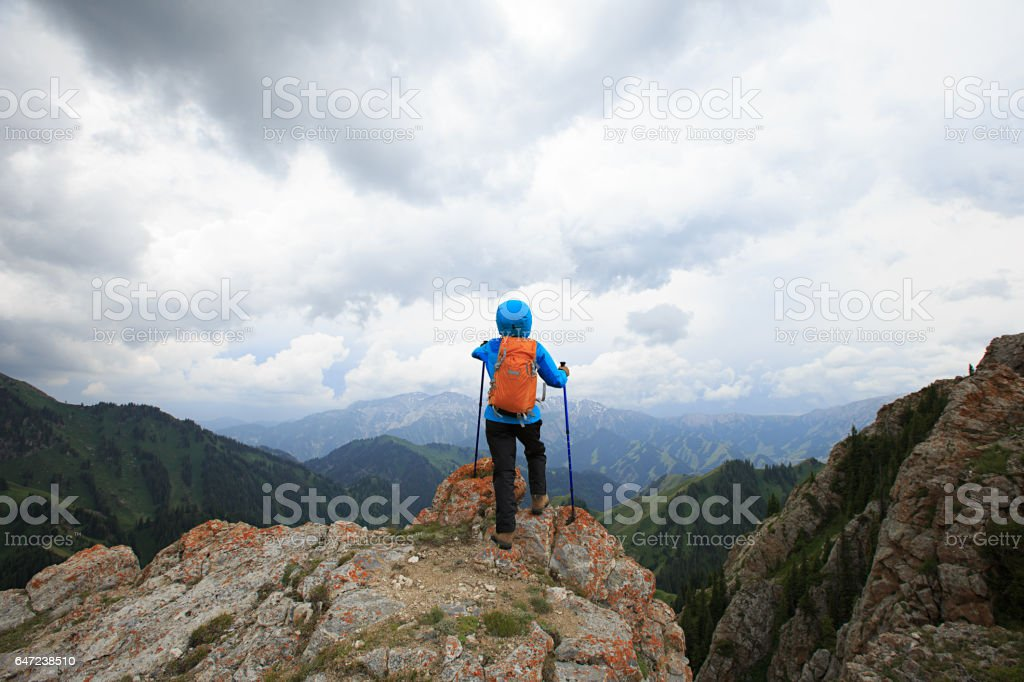 successful woman backpacker hiking on mountain peak cliff stock photo