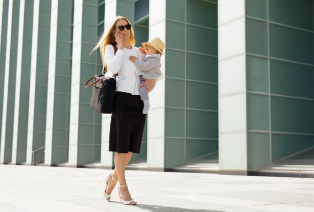 erfolgreiche frau mit baby in die hände arbeiten - kinder die schnell arbeiten stock-fotos und bilder