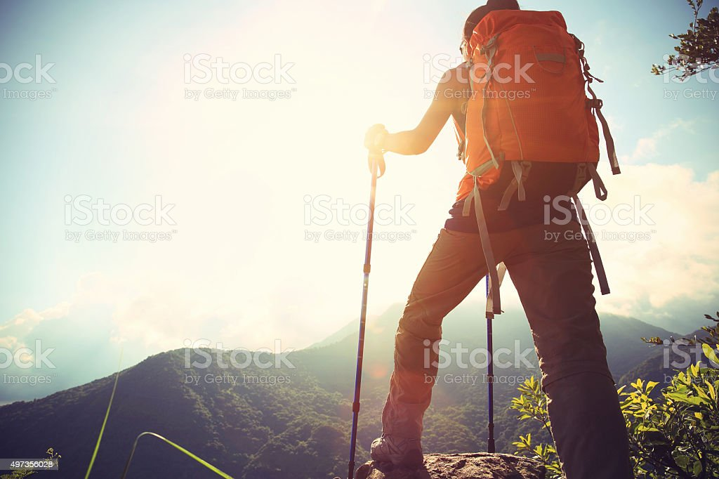successful woman hiker climbing to mountain peak stock photo