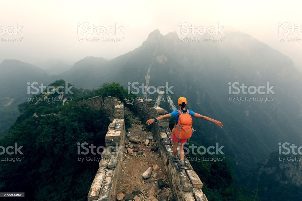 successful woman hiker open arms to the great wall on the top of mountain royalty-free stock photo
