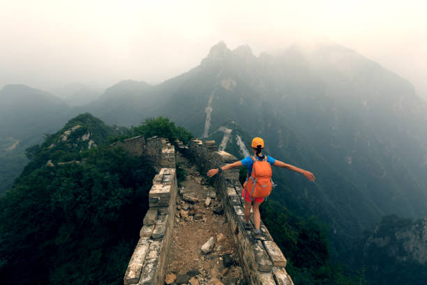 successful woman hiker open arms to the great wall on the top of mountain stock photo