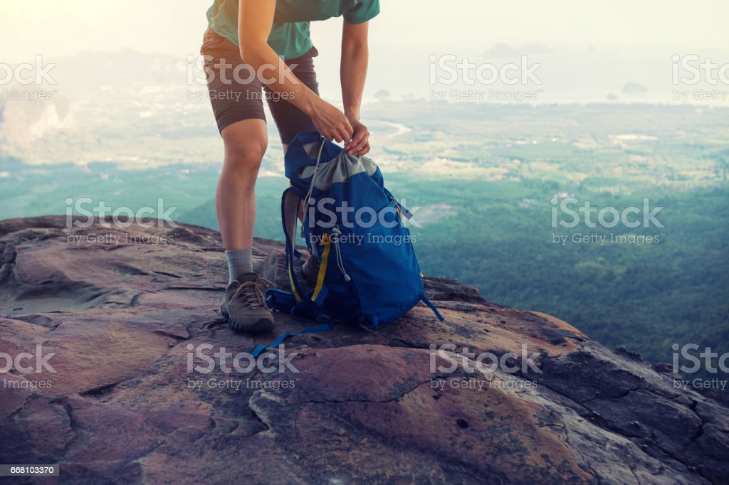 successful woman hiker packing the backpack hiking on mountain peak