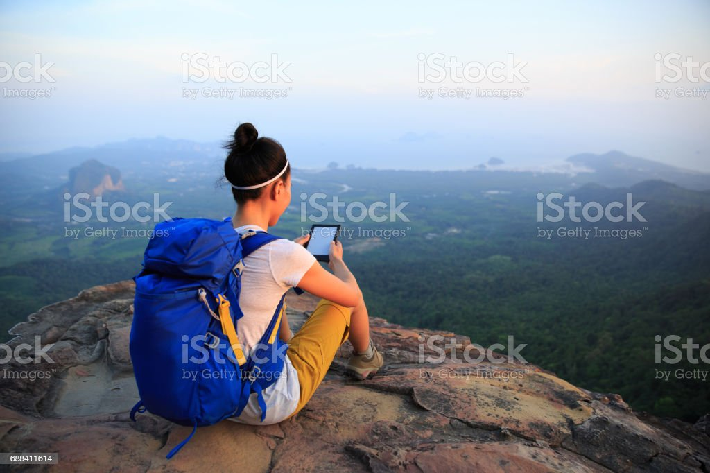 successful woman hiker reading e-book on mountain top stock photo
