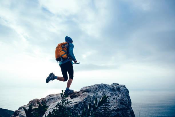 Erfolgreiche Wanderin läuft auf den Gipfel der Klippe am Meer – Foto