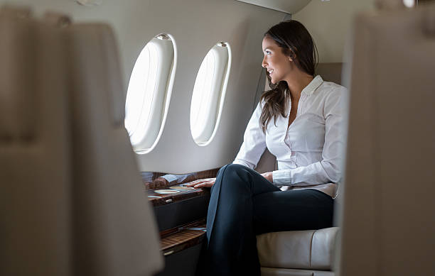 Successful woman in a business trip Successful woman in a business trip traveling by plane first class stock pictures, royalty-free photos & images