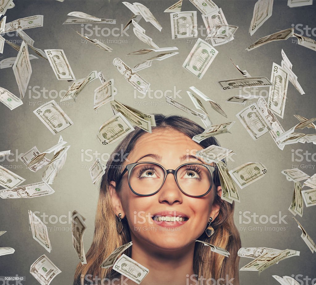successful woman in glasses looking up under money rain stock photo