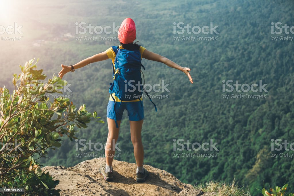 successful woman outstretched arms on mountian top stock photo