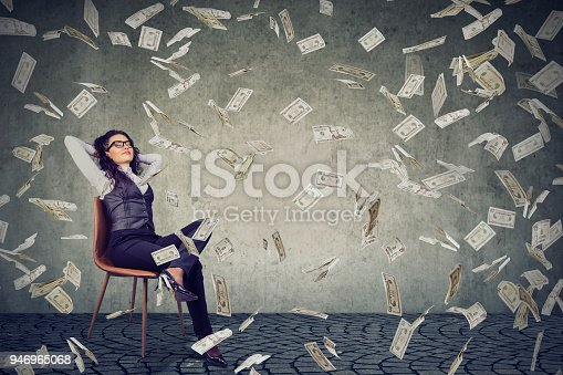 Young content woman sitting on chair in rain of flying bills happy with financial independence.