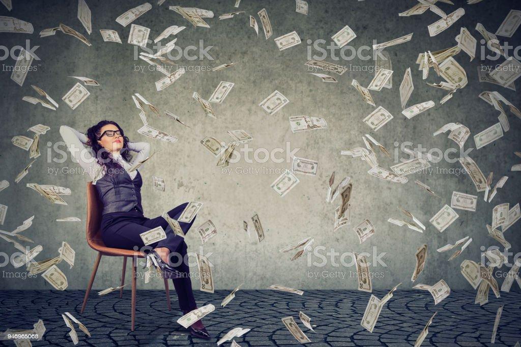 Erfolgreiche Frau sitzen unter Geld-Regen – Foto