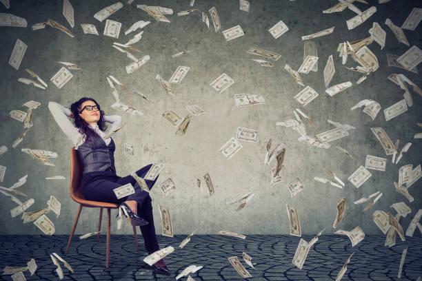 Successful woman sitting under money rain stock photo