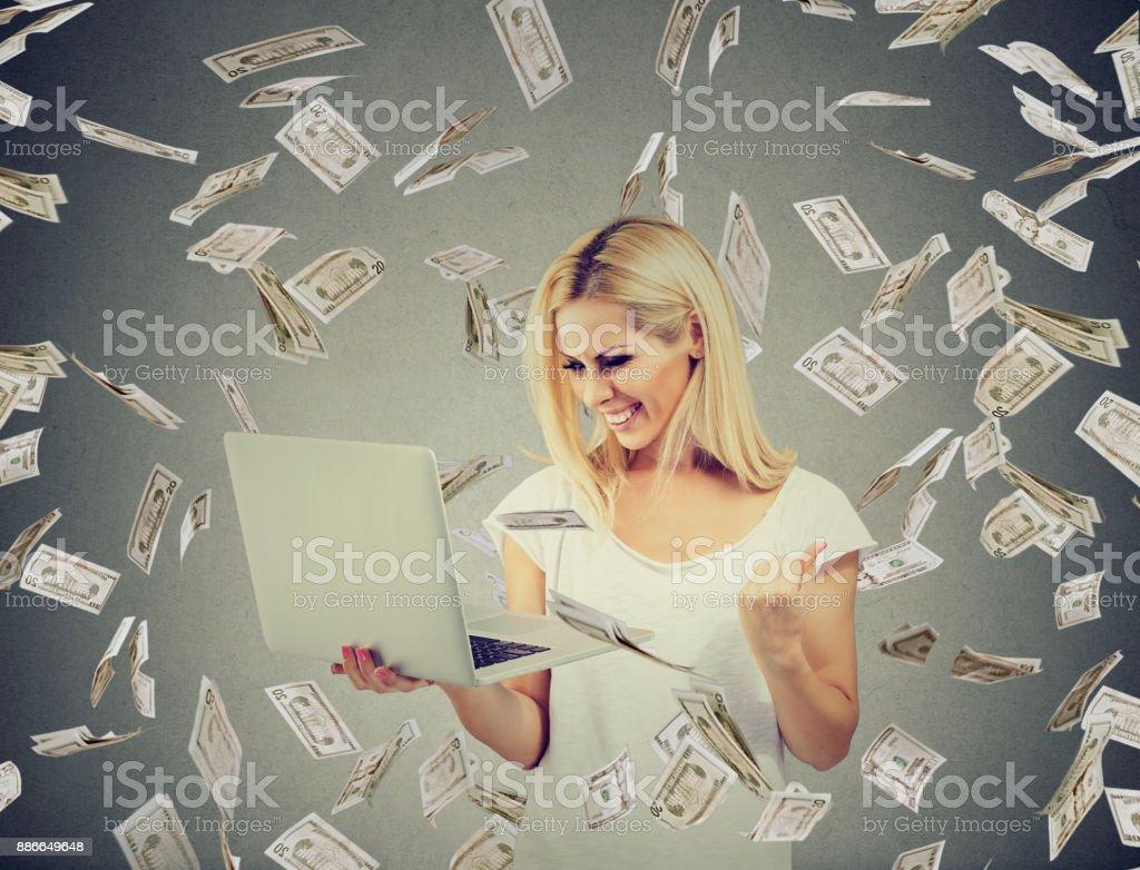 Successful woman using laptop building online business making money dollar bills cash falling down. Beginner IT entrepreneur success economy concept'n stock photo