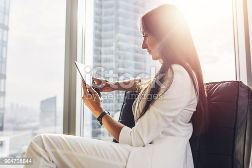 istock Successful woman wearing suit sitting on armchair using tablet computer at her loft apartment in city center 964728644